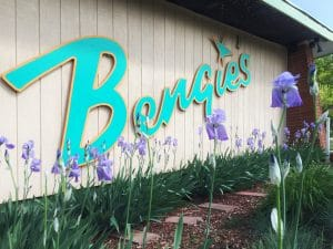 Iris in bloom in front of bengies drive-in theatre sign